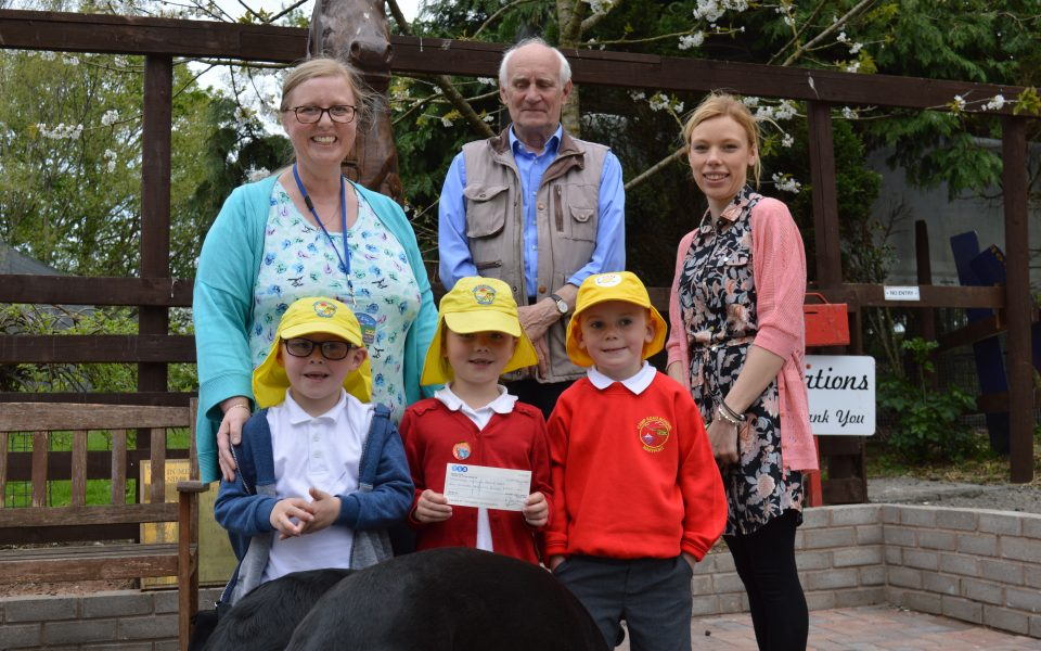 Maryport Infants School present George with a cheque.